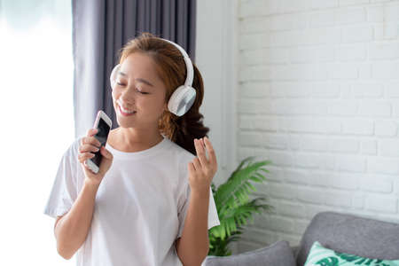 Asian women are listening to music and she sings in the room happily.