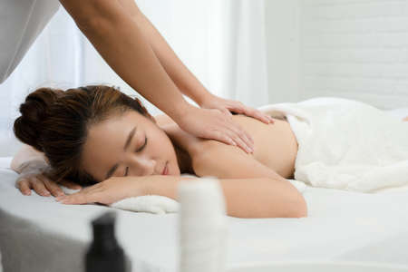 Beautiful Asian woman relaxing with hand massage at beauty spa.