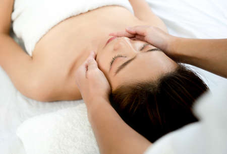 Closeup face of a beautiful Asian woman to face massage in the spa. Beauty health concept. Banco de Imagens - 165358429