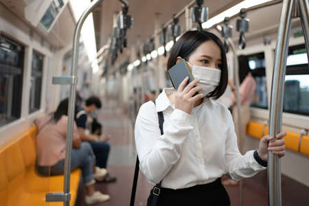 Asian woman wearing a mask in the subway. She is using her phone while traveling in a big city. Concept of infection and outbreak.