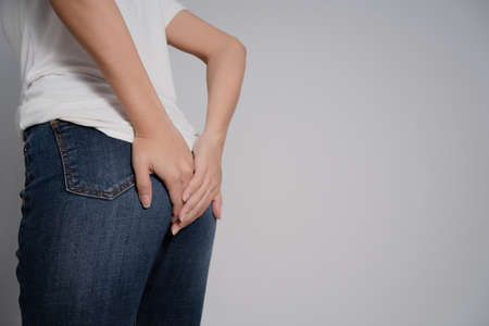 Asian woman has diarrhea. She used her hand to hold the behind. On a separate background.