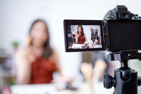 The camera is recording a video, a beautiful Asian blogger teaching you how to use makeup in the room. Archivio Fotografico