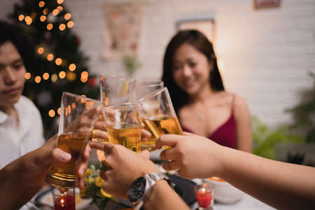Group of Asian people have a dinner and beer party at home. They clink a glass of beer. Stock Photo