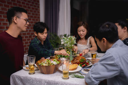 Group of Asian friends have a party and are eating at home.