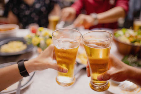 Close-up of people cheering of beer at a party. Group of Asian people having a New Year's party at home.