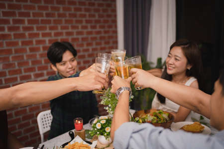 Group of Asian friends clink glasses of beer at a party. They are very happy and have fun.
