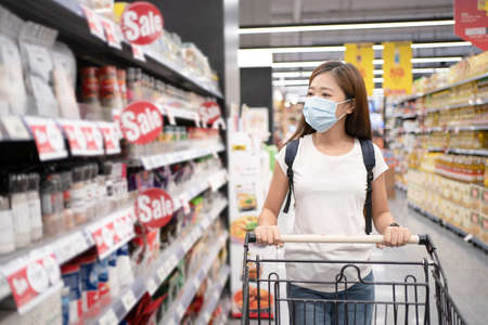 Young Asian women are shopping at supermarkets. She wears a mask against COVID-19 and dust.