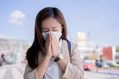 Asian woman wearing a N95 mask to prevent PM 2.5 dust. She is going to work. Banco de Imagens - 165367091