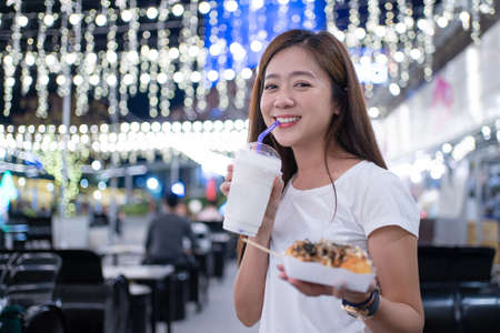 Asian woman tourists eating street food in Thailand in the evening. Banco de Imagens - 165367095