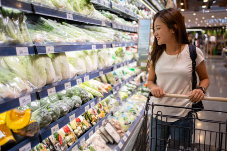 Asian woman is choosing green vegetables on the shelves in supermarkets. Banco de Imagens - 165367096