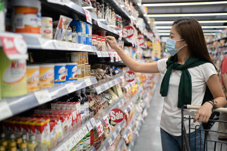 Nakhon Ratchasima, Thailand, 11 Dec 2020: Young Asian women wearing masks are selecting products on the shelves at the supermarket. Banco de Imagens