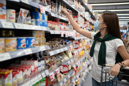 Young Asian woman wearing a mask looks at the product on the shelf at a supermarket. Banco de Imagens