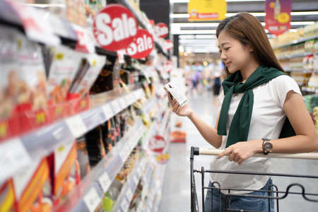 Smiling Asian woman shopping in a supermarket and reading product information. Banco de Imagens - 165367103