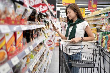 Asian young women reading product information on supermarket shelves. Banco de Imagens