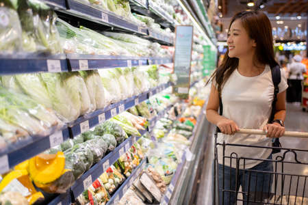 Young Asian woman is in a supermarket. She's looking for organic vegetables on the shelves at the supermarket.