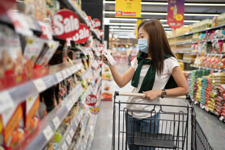 Young Asian woman wearing a mask is reading product information on a supermarket shelf.