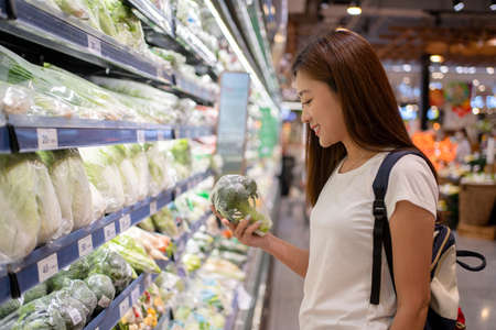 Asian womanin a supermarket is choosing green vegetables on the shelves, a concept of agriculture and a vegetarian diet. Banco de Imagens