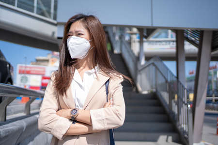 Asian woman wearing a N95 mask is going to work to prevent PM2.5 dust in the heart of the city. Banco de Imagens