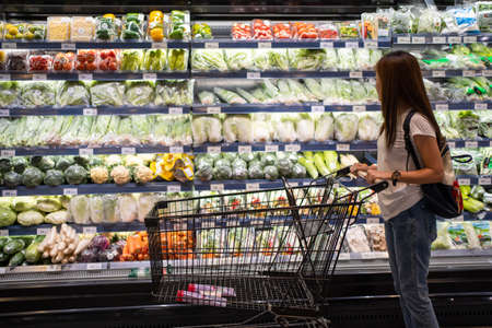 Asian woman is looking for organic vegetable in the shelf at supermarket. Banco de Imagens
