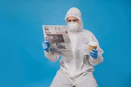 Asian doctors in protective suit with gloves and mask. She is reading the newspaper and hot coffee in hand. Imagens
