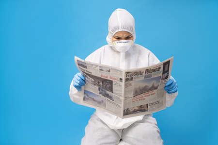 Asian woman in protective clothing with gloves and mask. She is reading a newspaper about COVID-19.