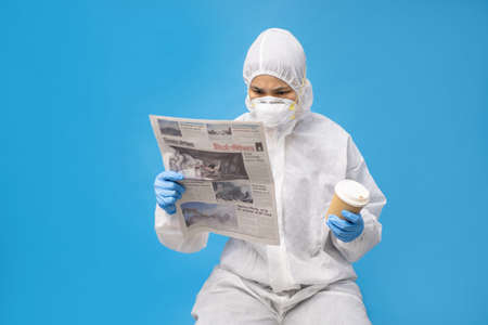 Asian doctors in protective suit with gloves and mask. She is seriously reading the newspaper and hot coffee in hand.