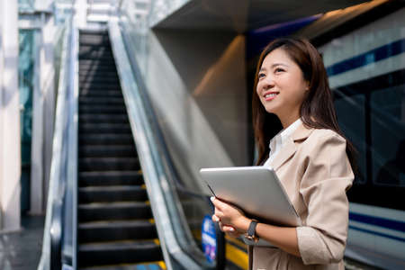 Asian business women going to work in the morning on the subway She was smiling and was holding a laptop.