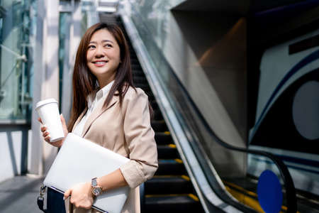 Asian business women going to work in the morning on the subway She was smiling in her hand holding a laptop and hot coffee. Imagens