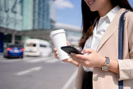 Young business women reading information on the internet while walking outdoors.