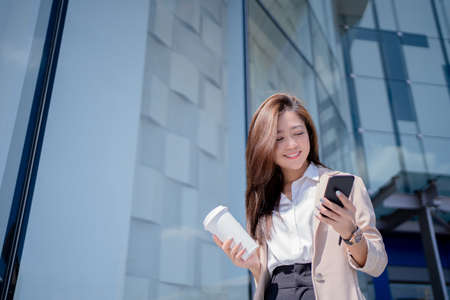 Professional Asian businesswoman drinking coffee and reading online while walking outdoors. Near her office