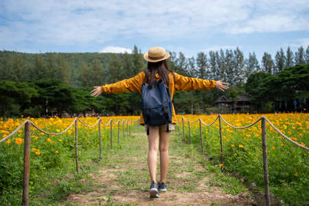 Asian woman tourists. She relaxes in a flower field.