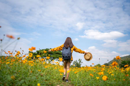Asian woman tourist relax and walk in yellow flower fields.