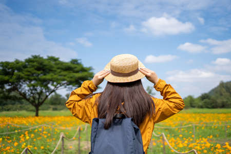 Young Asian women tourists relax in flower fields. She used her hand to hold her hat.