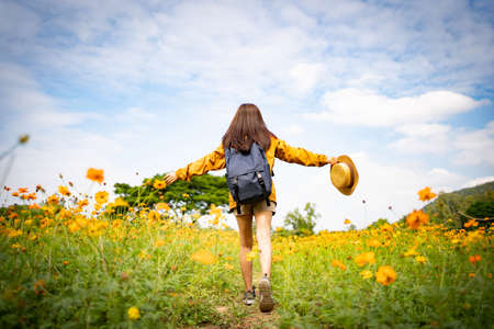 Asian female tourists enjoyed and walked in flower fields. Imagens