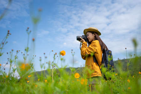Young asian women tourists. She was taking a picture with a camera in a flower field.