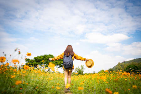 Asian woman tourists is happily running on a flower field.