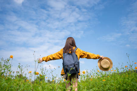Young Asian woman tourists relax in flower field on bright sky background. She used her hand to hold her hat. Imagens