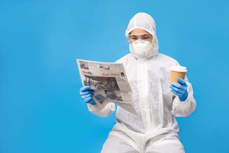 Asian people in protective clothing complete with gloves and masks. She is reading a newspaper and hot coffee in the studio on a bright blue background.