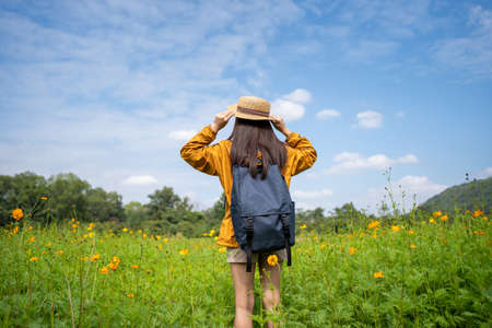 Young Asian women tourists relax in flower fields. She is traveling alone Imagens