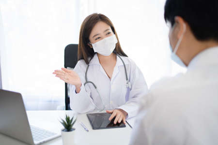 Young Asian doctor wearing a preventive mask is explaining to a patient in a hospital room. Concept to consult a doctor