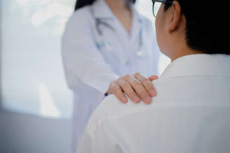 Female doctor put hand on patient shoulder for encouragement and discussion. Doctor and patient.