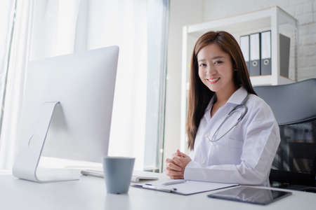 Female doctor working at office desk and smiling at camera with office interiors on the background. Imagens