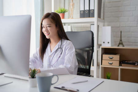 Asian woman doctor in a white coat works on a personal computer in a hospital.