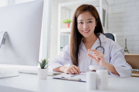 Young woman doctor or pharmacist sitting at a desk holding a medicine in her hand. Concept of medical care pharmacy.