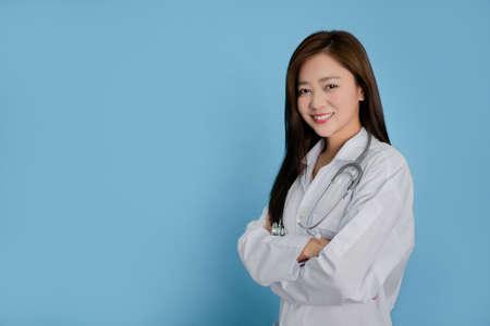 Beautiful female doctor isolated on blue background.