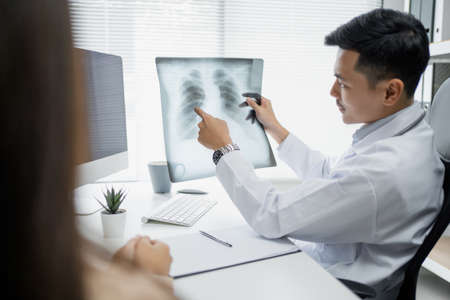 Expert doctor is examining and explaining the x-ray film to the patient.