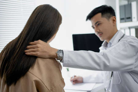 Male doctor is consoling the patient in the examination and x-ray of the disease. He was holding onto her shoulder. Imagens