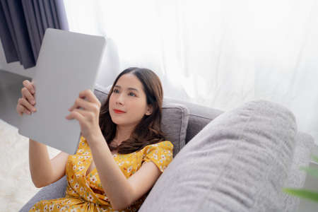 Young asian women work at home She is resting, using social media, following the news and relaxing.