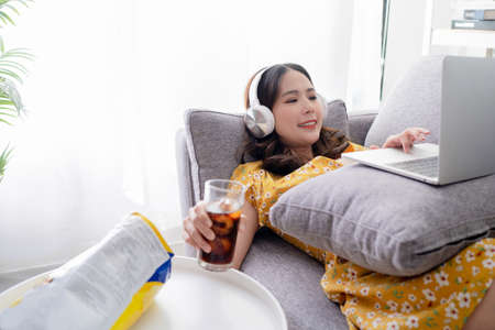 Young Asian woman are relaxing using social media, follow news on tablet. She works at home. Imagens
