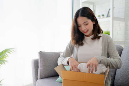 Asian woman are happy sitting on sofa at home. She is opening a paper box received from an online order. Easy and fast service commerce delivery concept